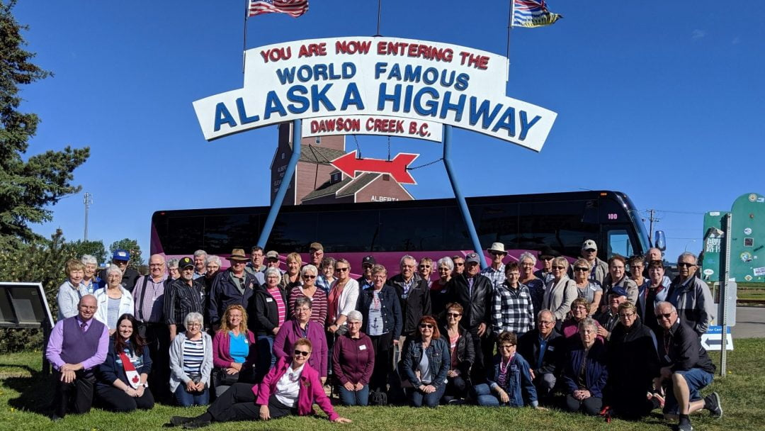 tour group at mile zero of Alaska Highway